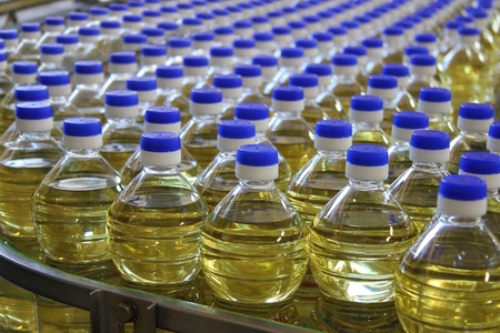 Sunflower oil in the bottle moving on production line photo