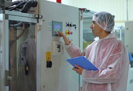 quality: Worker controls the sugar packing machine Stock Photo