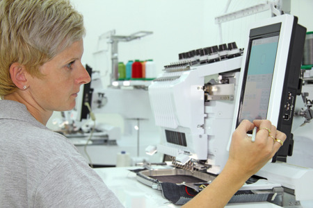 workwoman: Woman working on computerized machine embroidery in a factory