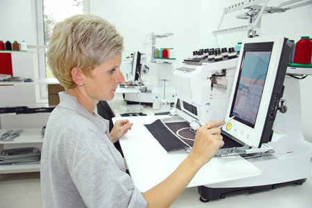Woman working on computerized machine embroidery in a factory photo