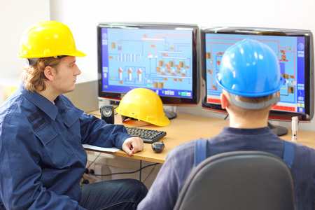 Industrie-arbeiders in de controlekamer Stockfoto