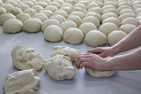 food processing: Female baker kneading dough in a bakery