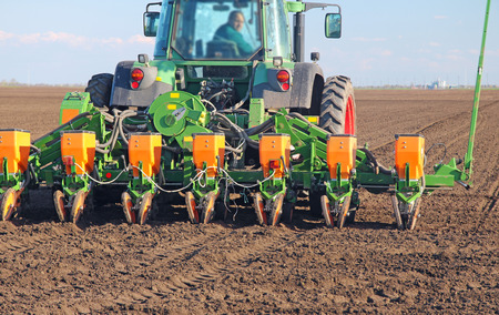 seeding: Agricultural tractor sowing and cultivating field Editorial