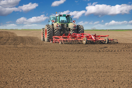 Agricultural tractor cultivating field, preparing for sowing