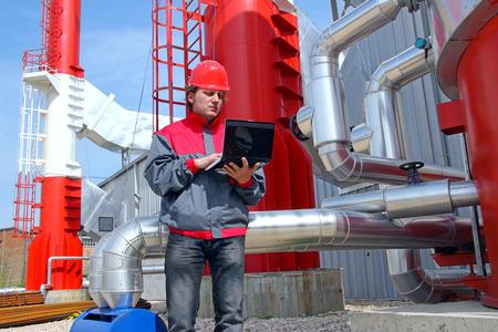 casco rojo: Trabajador industrial con el cuaderno de trabajo en la planta de energía