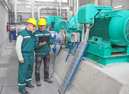 Industrial workers with notebook, teamwork Stockfoto