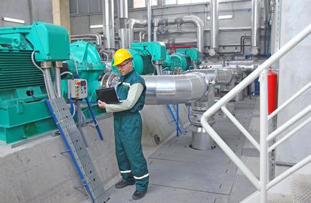 Industriële werknemer met een notebook die werkzaam zijn in centrale