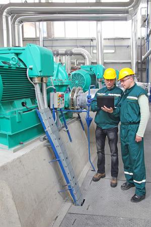 Industrial workers with notebook, teamwork Standard-Bild