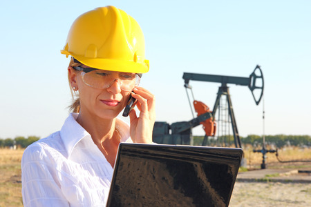 Business woman in an oilfield talking on cell phone