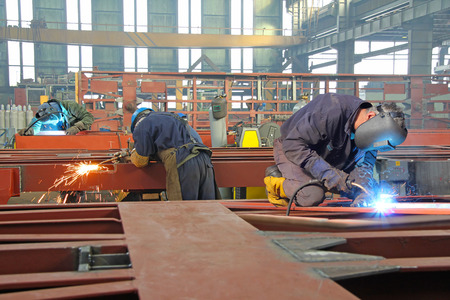 Steel workers welding, grinding, cutting in metal industry photo
