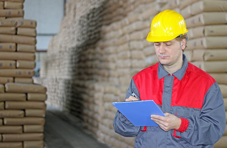 Worker writing on clipboard in warehouse, sugar bags photo