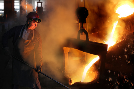 Hard work in the foundry, worker controlling iron smelting in furnaces, too hot and smoky working environment