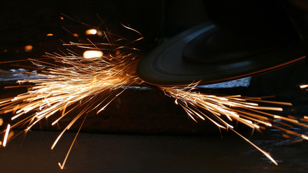 Worker grinding a metal construction with grinding wheel, lots of sparks in factory Stock Photo