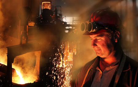 Hard work in the foundry, worker watching and controlling iron smelting in furnaces, too hot and smoky working environment photo