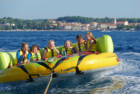 POREC, CROATIA - AUGUST 10. 2016. Enjoyment on the sea vacation, kids having great fun on crazy ufo, water sport on the beach