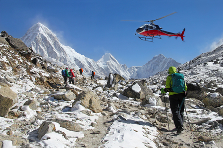 Goup of climbers in the Himalayas, view on peaks Lingtren, Pumori and Khumbutse. Rescue helicopter in action, Nepal Editorial