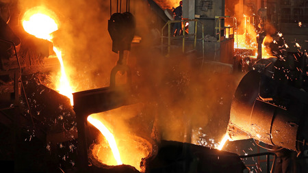 Liquid metal in the foundry, melting iron in furnace, steel mill. Workers controlling iron smelting in furnaces Imagens