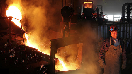Hard work in foundry, liquid metal in the foundry, melting iron in furnace, steel mill. Workers controlling iron smelting in furnaces