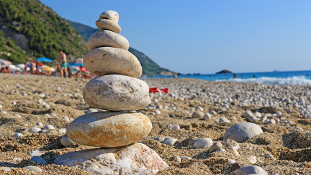 Stones balance on beach, people sunbathe, swim and enjoy on sea vacation