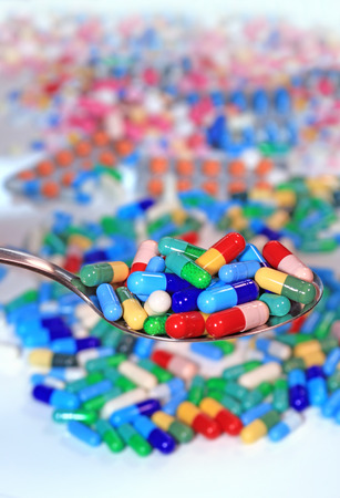 Full of spoon of capsules, medical treatment with a high dose of drugs. Colorful pills and tablets on table