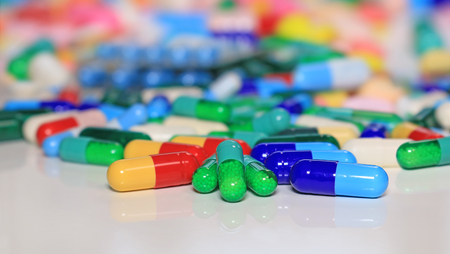 Colorful tablets with capsules and pills on white table, concept of medical treatment