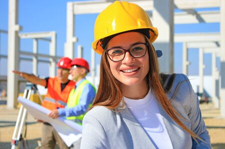 Gelukkig mooie vrouwelijke architect op bouwplaats. Ze lacht en is tevreden met haar werk, achter haar bouwingenieurs die plannen maken en praten over het project, teamwork Stockfoto