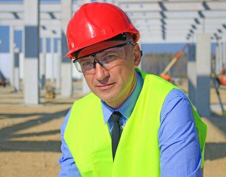 Retrato de gerente de construcción con gafas de seguridad y chaleco de trabajo. Está satisfecho con su trabajo, mira a la cámara, concepto de empresario
