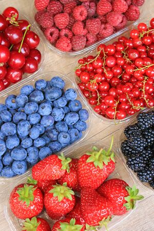 Mix of fresh berries on wooden background, strawberry, blueberry, raspberry, blackberry and red currant Imagens - 140520718