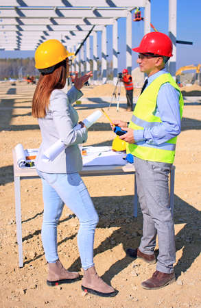 Female architect and construction engineer in hardhats talking about the project on construction site, behind them construction worker with measuring device, crane and construction workers, teamwork Imagens