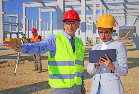 Female architect with tablet and construction engineer in hardhats talking about the project on construction site, behind them construction worker with measuring device, teamwork