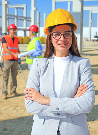 Happy beautiful female architect on a construction site. She is smiling and satisfied with her job, behind her construction engineers shaking hands, positive emotions, joy and smiles