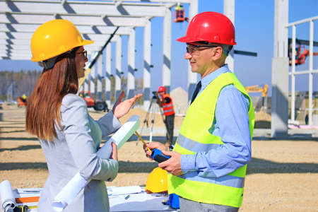 Female architect and construction engineer in hardhats talking about the project on construction site, behind them construction worker with measuring device, crane and construction workers, teamwork