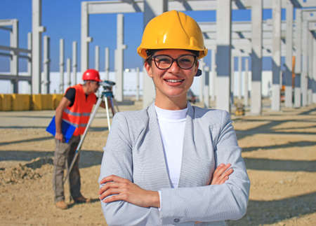 Happy beautiful female architect on construction site. She is smiling and satisfied with her job, behind her construction engineer with measuring device, positive emotions, joy and smiles