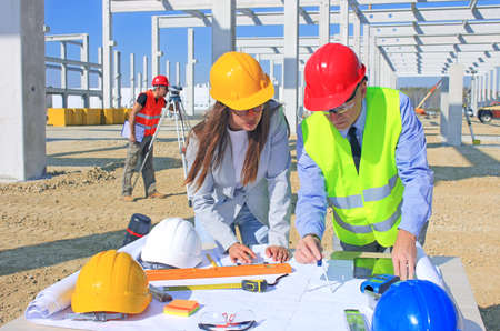 Female architect and construction engineer in hardhats talking about the project on construction site, behind them construction worker with measuring device, teamwork