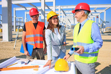 Female architect, construction engineer and manager talking about the project on construction site. Teamwork - group of builders and architect in hardhats, positive emotions, joy and smiles Imagens