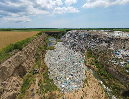 Garbage dump pollution, lots of plastic bags, environmental pollution landfill near the city. Nature destruction, plastic bottles rubbish and waste, unhealthy life Imagens