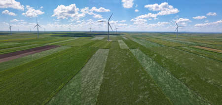 Aerial view of wind turbines in corn and soybean field. Beautiful summer landscape with wind farm and clouds in the blue sky. Energy production with clean and renewable energy