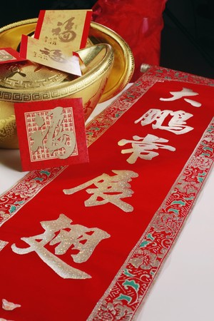 auspicious: Chinese New Year banner with auspicious idioms with golden ingot and red packets at its side Stock Photo