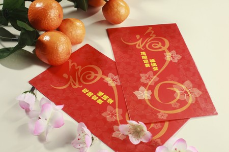 Red packets with mandarin oranges and plum blossoms photo