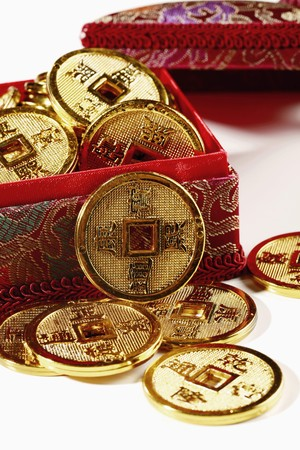 Red box overflowing with antique chinese coins
