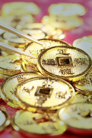 Chopsticks about to pick up an antique chinese coin Stock Photo - 4186922