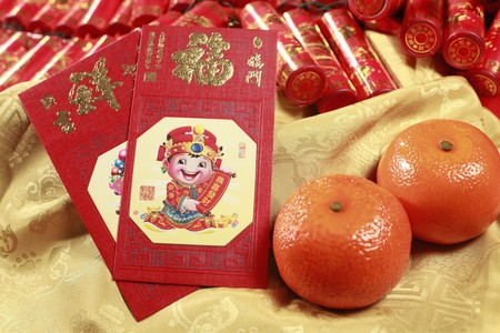 Red packets and mandarin oranges, firecrackers in the background Stock Photo - 4186974