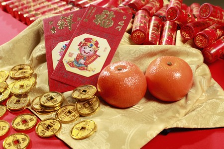 Red packets, antique chinese coins and mandarin oranges, firecrackers in the background Stock Photo - 4186975