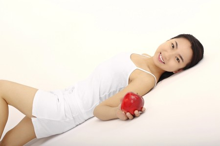 Woman lying on the floor, holding a red apple photo