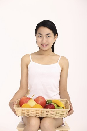 Woman holding a basket of fruits while sitting on chair photo