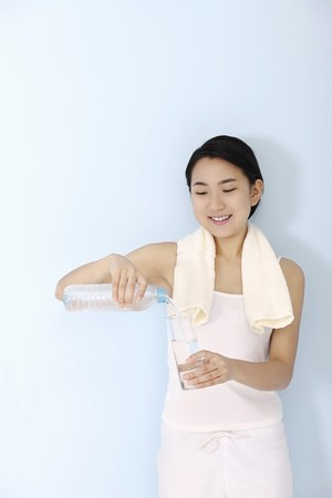 Woman with towel around her neck, pouring water into glass photo