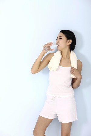 Woman with towel around her neck, enjoying a glass of water Stock Photo
