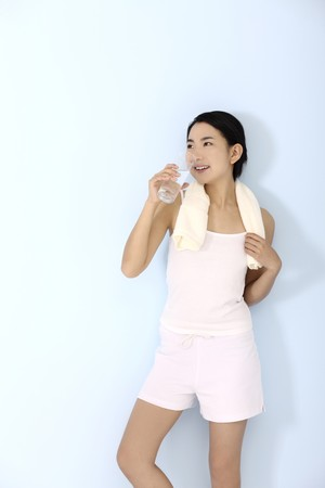 Woman with towel around her neck, enjoying a glass of water photo