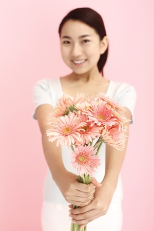 Woman smiling while holding flowers photo