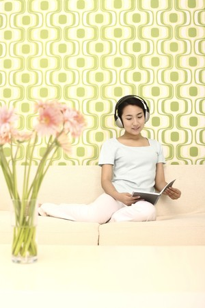 Woman listening to music while reading photo